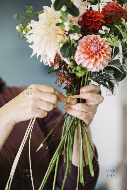 Organic flower arrangements. A woman creating a hand tied bouquet.