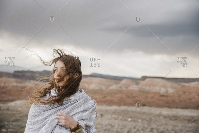 A woman with long hair blowing in the wind standing in a desert landscape.