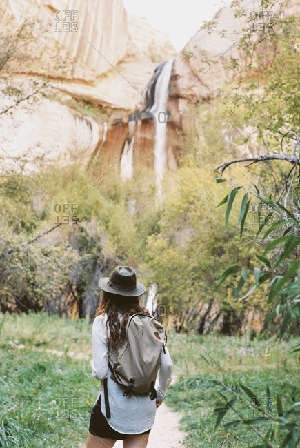 A woman carrying a backpack, walking under a tall cliff in a canyon. Waterfall.
