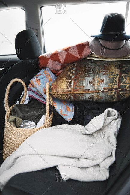 Close up of items on the back seat of a car, cushions, hats and a bag and blanket.