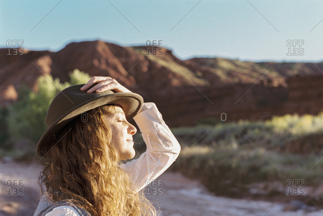 A woman wearing a hat standing in open space with mountains, face towards the sun.