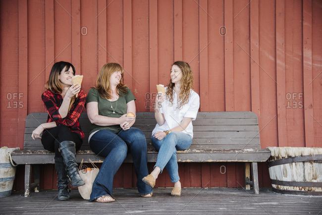 Three women sitting on a bench, eating ice cream.