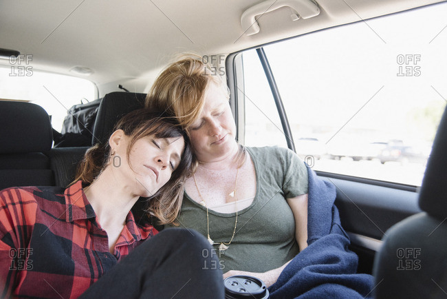 Two women in a car on a road trip, both asleep in the back seat, heads together.