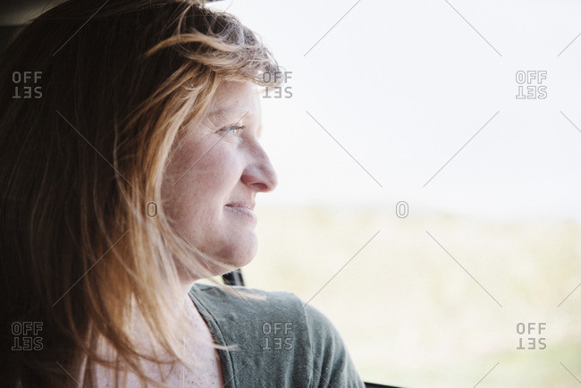 Woman in a car on a road trip, looking out of the window.