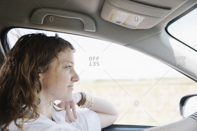 Woman in a car on a road trip, in the driving seat, elbow on the door.