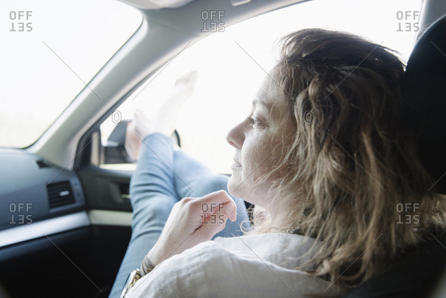 Woman in a car on a road trip, her legs and bare feet out of the window.