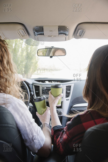 Two women in a car holding coffee cups. View over shoulder.