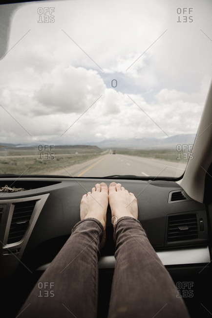 A woman in a car with bare feet on the dashboard.  View of the road ahead.
