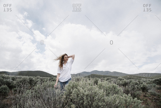 A woman standing in an open landscape with a view of mountains woodland and scrub land.