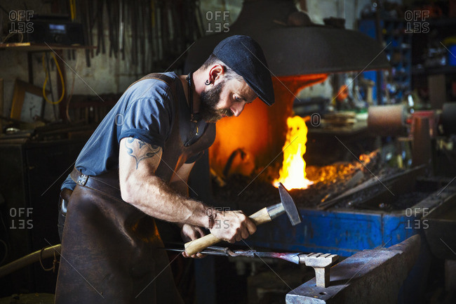 A blacksmith uses complex tools to hammer a cone of red hot metal on an anvil in a workshop.