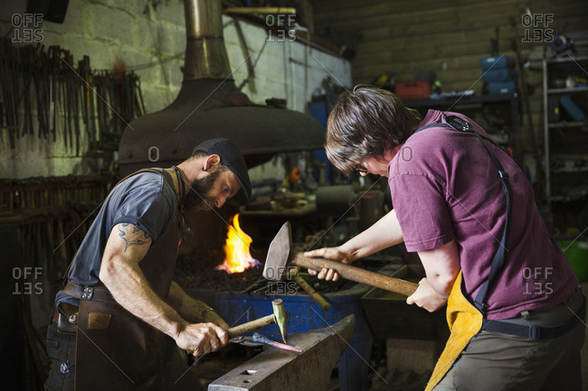 Two blacksmiths hammer a piece of metal on an anvil in a workshop