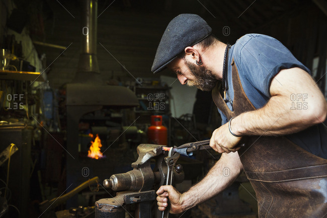 A blacksmith in a leather apron bends a cone of red hot metal in a vice using a wrench and a pair of tongs.