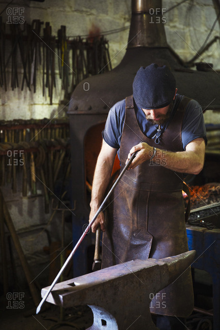 A blacksmith in a leather apron holds a thin length of metal against an anvil in a workshop.