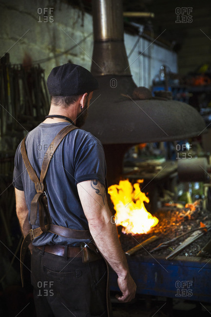 A blacksmith wearing a leather apron stands in front of a furnace in a workshop.