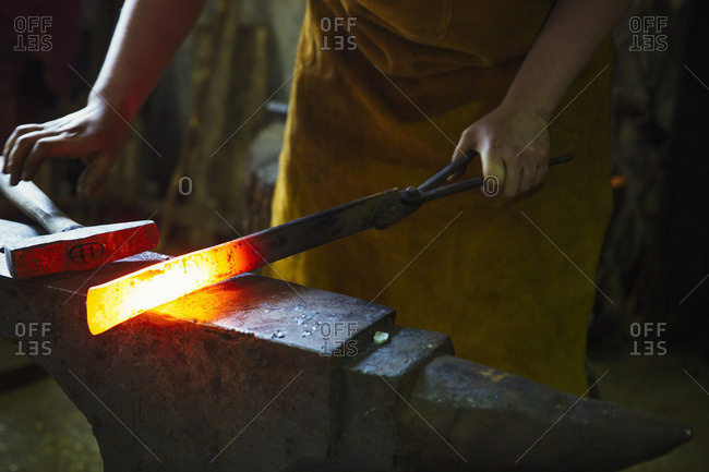 A blacksmith holds a length of red hot metal on an anvil with a pair of tongs.