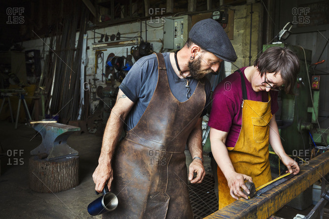 Two blacksmiths measure a length of metal in a workshop.