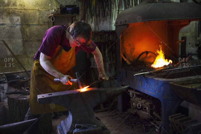 A blacksmith striking red hot metal on an anvil inside a workshop.