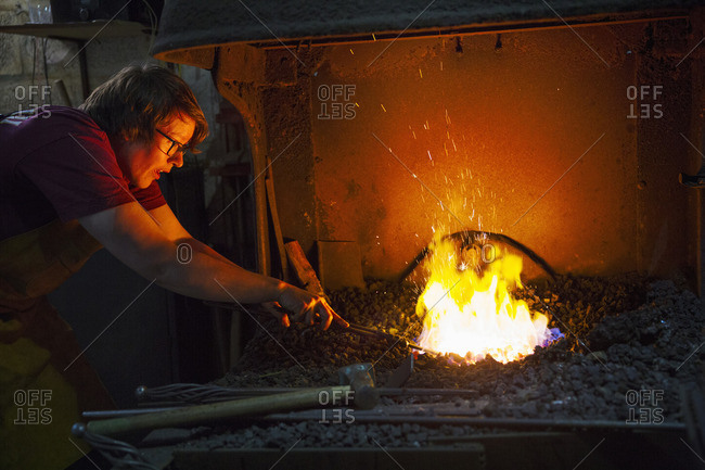 A blacksmith using tongs to heat something in a furnace.
