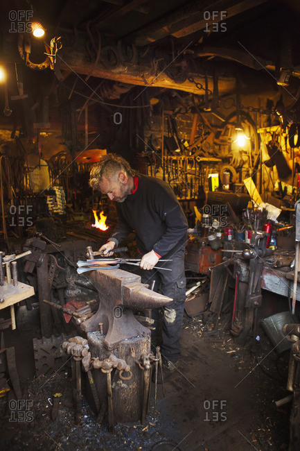 Blacksmith standing at an anvil in his workshop.