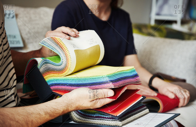 Two people sitting on a sofa, looking at a selection of fabric samples.