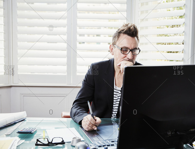 A man wearing glasses sitting at a desk in an office looking at a computer screen.