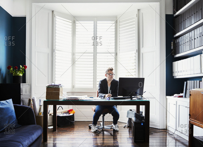 A man in suit and trainers with glasses, sitting at a desk in a bay window
