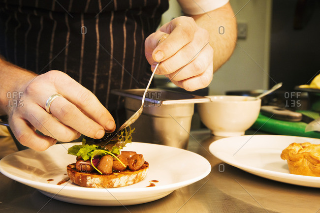 Village public house restaurant. A chef plating up a dish of meat and vegetables.