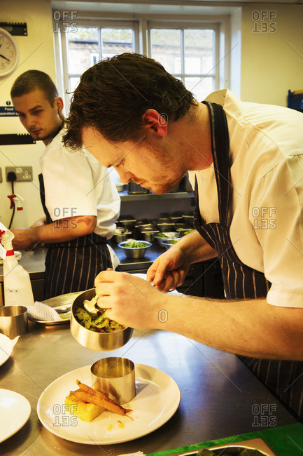 a Village public house kitchen. A chef plating up a dish, with care and precision.