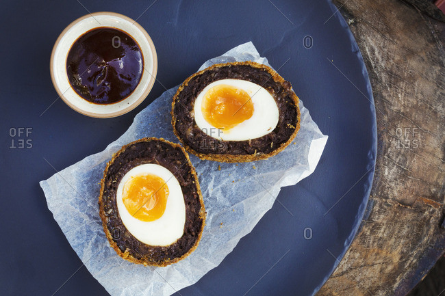 Village pub food. A blue dish with a fresh made scotch egg cut in to two and a pot of sauce.