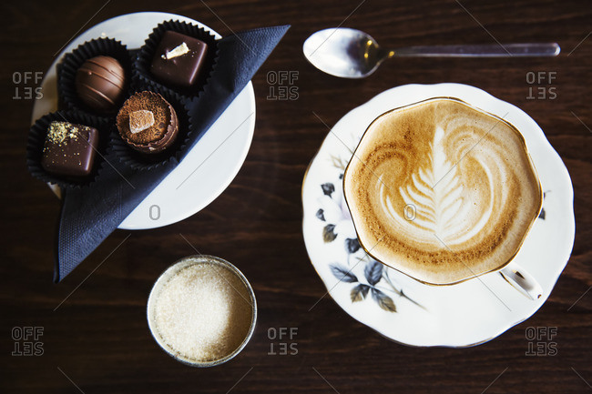 Assorted hand made chocolates on a plate.  A cup of coffee with a pattern in the foam top.