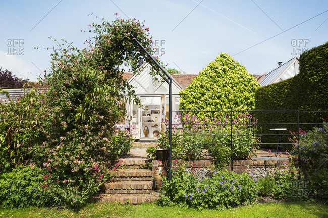 A garden pergola with climbing plants, and a historic house in a village.
