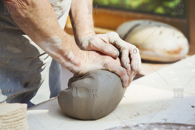 A person, potter preparing a lump of damp clay for throwing.