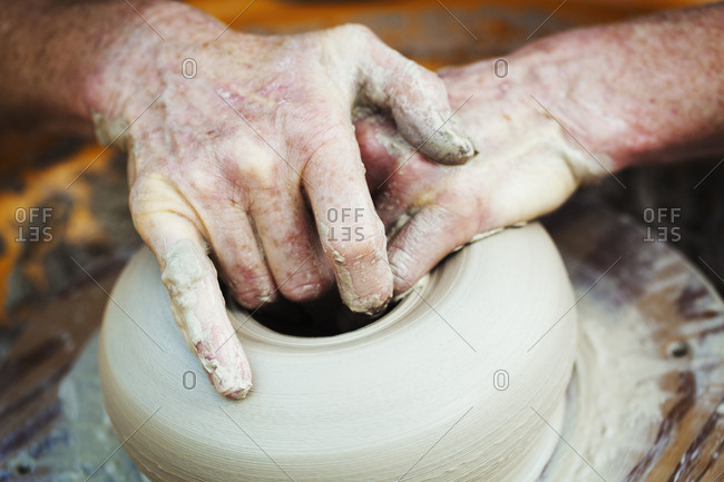 A woman potter working clay on a potter's wheel in her workshop.