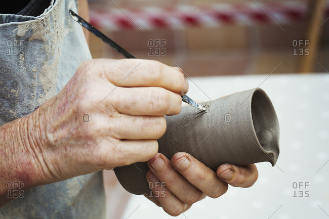 A potter handling a wet clay pot and marking a design on the outside, preparing it for kiln firing.