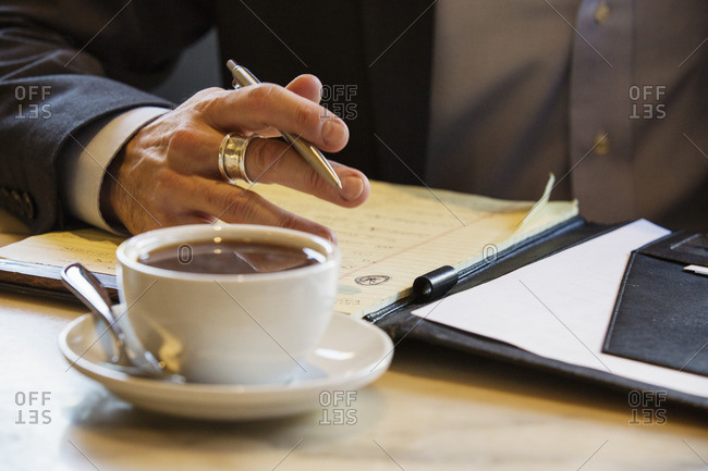 Businessman sitting in a cafe, coffee cup standing on a table.