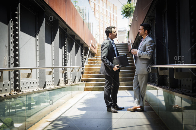 Two businessmen wearing grey suits standing outdoors, talking to each other.