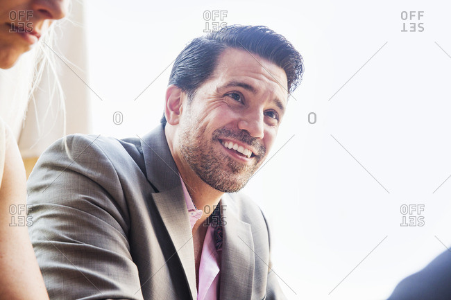 Smiling businessman wearing a grey suit and pink shirt.