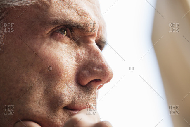 Close up of a man's face, his hand on his chin, looking into the distance.