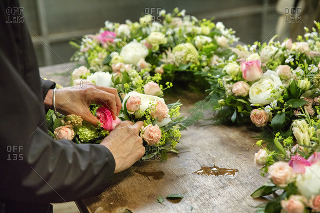 Commercial flower arranging. A florist, a woman working on a floral decoration at a workbench.