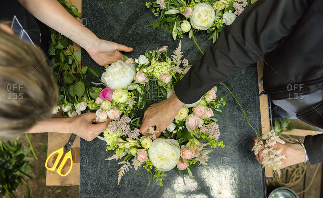 A florist's workshop. Overhead view of two women working on an arrangement.