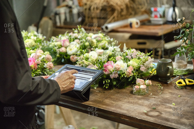 A woman in a florist's workshop using a digital tablet, at a workbench with flower arrangements.