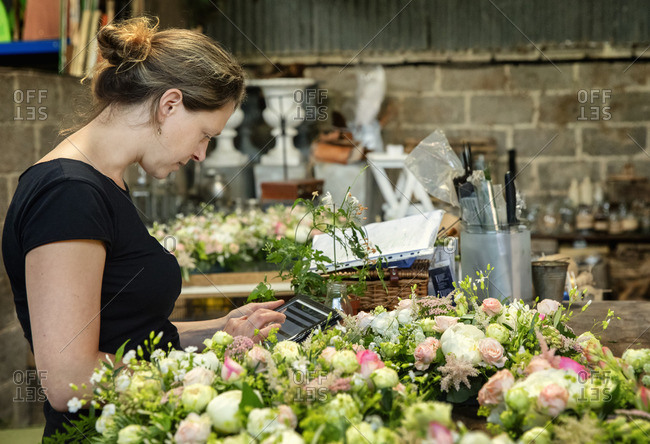 A florist working using a digital tablet by a workench of small flower arrangements.