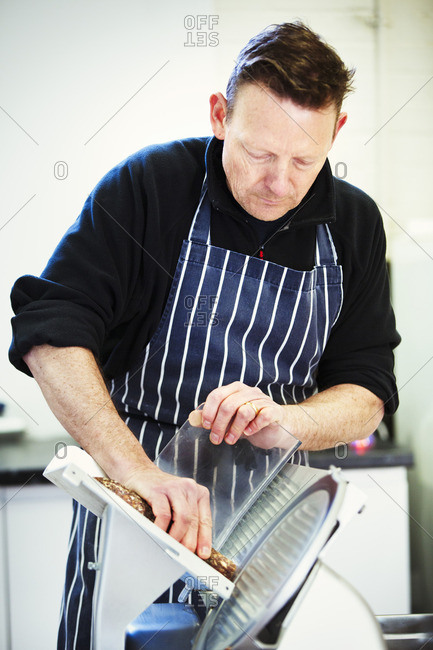 Butcher wearing a striped blue apron, slicing salami with a slicer.