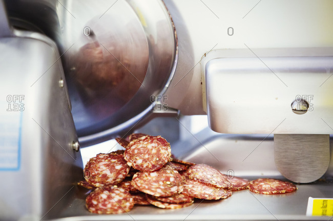 Close up of a pile of slices of salami lying next to a slicer.