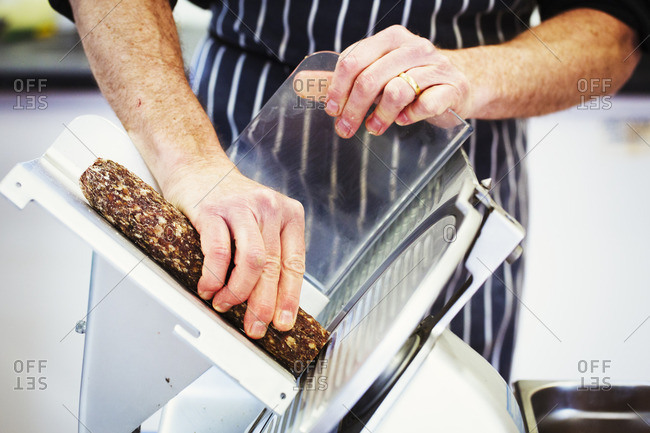 Close up of a butcher wearing a striped blue apron, slicing salami with a slicer.