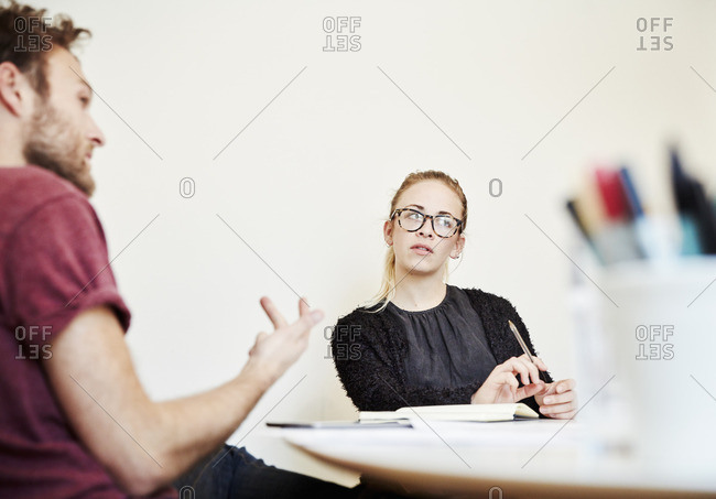 Two people at a meeting, a man gesticulating and a woman listening.