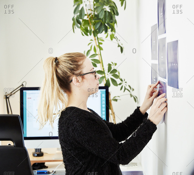 A woman sticking printed notes onto a wall, planning a project and creating a project management plan.