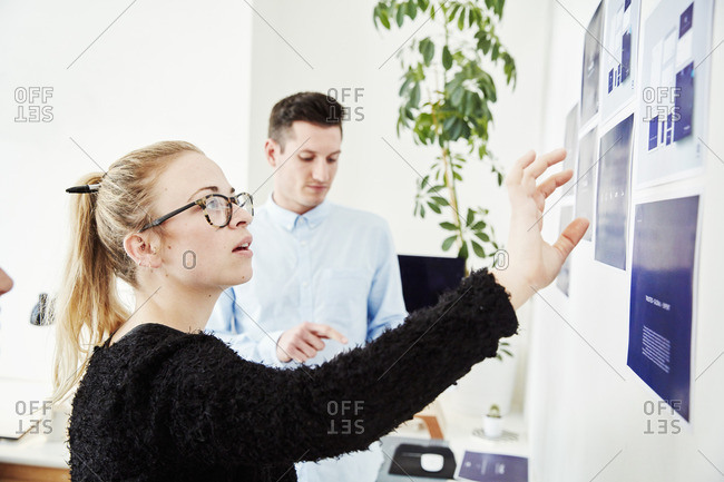 Two people looking at printed plans stuck on a wall, project management and discussions.