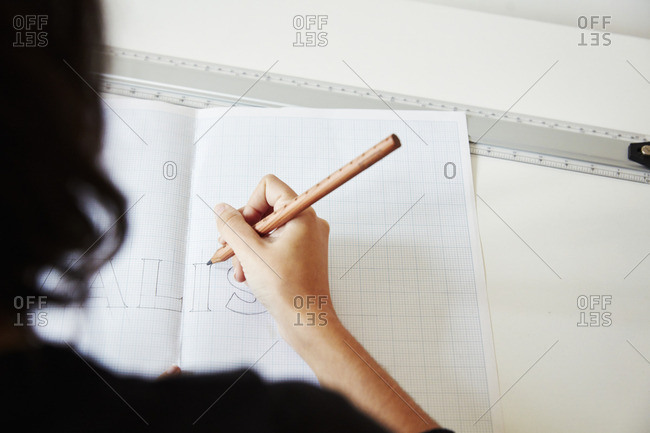 Over the shoulder view of a woman working on a graphic on a drawing board, outlining letters with a pencil.