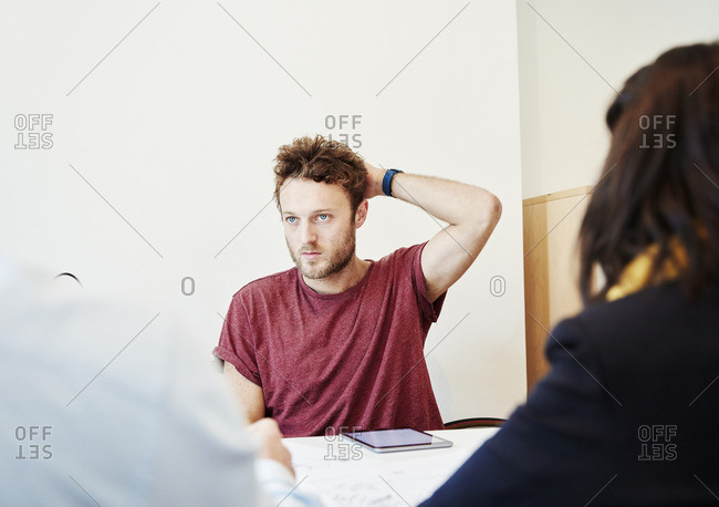 A man sitting in a meeting with two colleagues.
